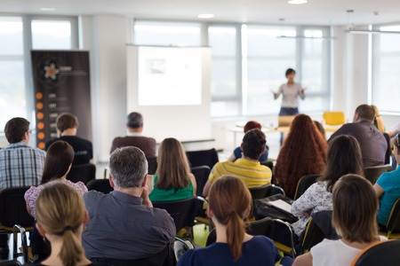 Business and entrepreneurship symposium. Speaker giving a talk at business meeting. Audience in conference hall. Rear view of unrecognized participant in audience. Stock Photo