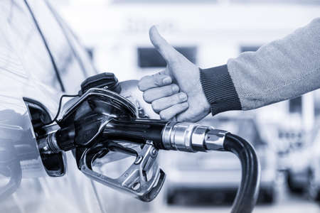 Petrol or gasoline being pumped into a motor vehicle car. Closeup of mans hand showing thumb up gesture, pumping gasoline fuel in car at gas station. Greyscale blue toned image.