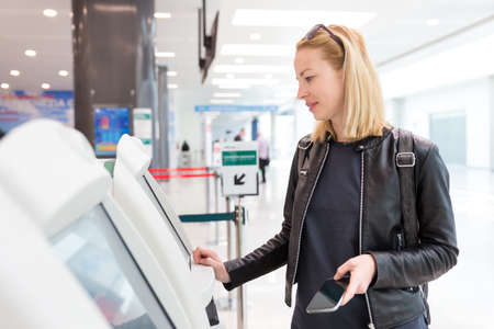Casual caucasian woman using smart phone application and check-in machine at the airport getting the boarding pass. Modern technology on airport. Stock Photo
