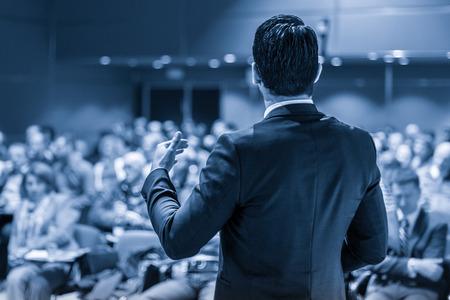 Altoparlante che dà un discorso sulla conferenza di lavoro aziendale. Persone irriconoscibili in udienza presso la sala conferenze. Evento di affari e imprenditorialità. Immagine in scala di grigi nei toni del blu.