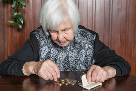 Elderly 95 years old woman sitting miserably at the table at home and counting remaining coins from the pension in her wallet after paying the bills. Фото со стока