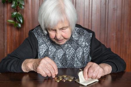 Une femme âgée de 95 ans assise misérablement à table à la maison et comptant les pièces de monnaie restantes de la pension dans son portefeuille après avoir payé les factures. Banque d'images
