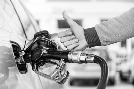 Petrol or gasoline being pumped into a motor vehicle car. Closeup of mans hand showing thumb up gesture, pumping gasoline fuel in car at gas station. Black and white image. 版權商用圖片