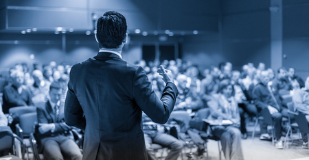 Speaker giving a talk on corporate business conference. Unrecognizable people in audience at conference hall. Business and Entrepreneurship event. Blue toned grayscale image. Stock fotó