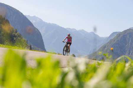 Active sporty woman riding mountain bike in the nature, Slovenia. 免版税图像