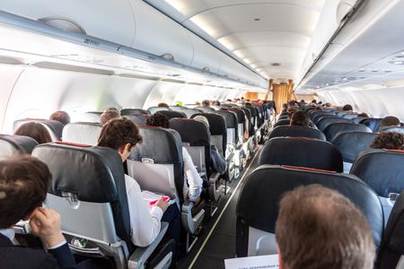 Interior de gran avión comercial con pasajeros irreconocibles en sus asientos durante el vuelo.