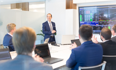 Businessman giving a talk in conference room. Business executive delivering presentation to business partners during business meeting. Corporate business concept. Stock Photo