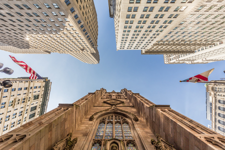 Wide angle upward view of Trinity Church at Broadway and Wall Street with surrounding skyscrapers, Lower Manhattan, New York City, USA.