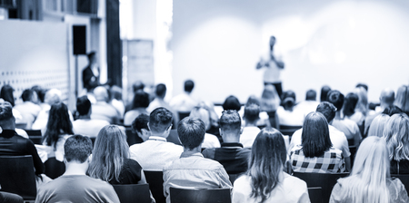 Sprecher hält einen Vortrag im Konferenzsaal bei einer Geschäftsveranstaltung. Konzentrieren Sie sich auf nicht erkennbare Personen im Publikum. Business- und Entrepreneurship-Konzept. Blau getöntes Graustufenbild.