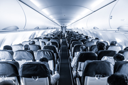 Interior of commercial airplane with unrecognizable passengers on their seats during flight shot from the rear of airplane. Black and white, blue toned image.