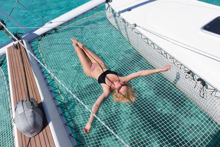 Womanin bikini che si abbronza e si rilassa in una crociera estiva in barca a vela, sdraiato sull'amaca di un catamarano di lusso vicino alla perfetta spiaggia di sabbia bianca sull'isola di Spargi nell'arcipelago della Maddalena, Sardegna, Italia Archivio Fotografico