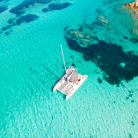 Drone aerial view of catamaran sailing boat in Maddalena Archipelago, Sardinia, Italy. Maddalena Archipelago is a group of islands between Corsica and north-eastern Sardinia. Stockfoto