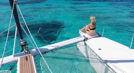Donna in bikini che si abbronza e si rilassa durante una crociera estiva in barca a vela, seduta su un lussuoso catamarano nella perfetta laguna blu turchese vicino all'isola di Spargi nell'arcipelago della Maddalena, Sardegna, Italia.