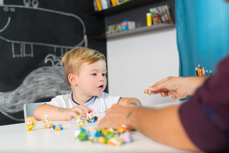 Cute little playfull toddler boy at child therapy session. Private one on one homeschooling with didactic aids. Stock Photo - 110783389