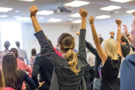 Simposio de coaching de vida. Orador dando un discurso motivacional interactivo en el taller de negocios. Vista posterior de participantes irreconocibles que se sienten empoderados y motivados, con las manos en alto en el aire.