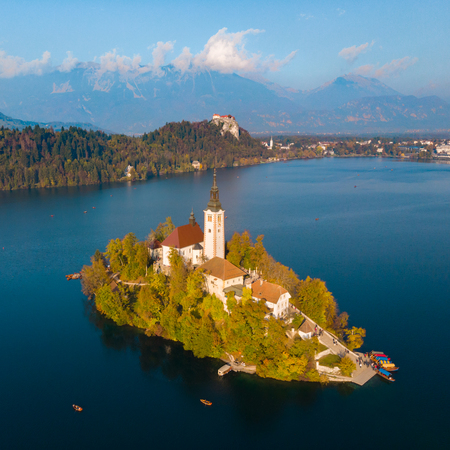Aerial view of Bled island on lake Bled, and Bled castle and mountains in background, Slovenia, Europe.