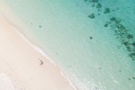 Aerial shot of woman looking up arms rised, enjoying the picture perfect white sand tropica beach on Mauritius island. Perfect tropical beach vacations concept.
