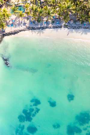 Aerial view of beautiful tropical beach front hotel resort with swimming pool, palm leaves umbrellas and turquoise sea. Paradise destination for vacations in Mauritius. Banque d'images