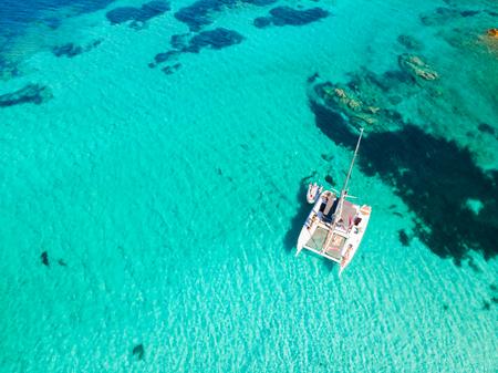 Drone vista aerea del catamarano in barca a vela nell'Arcipelago della Maddalena, Sardegna, Italia. L'arcipelago della Maddalena è un gruppo di isole comprese tra la Corsica e la Sardegna nord-orientale.