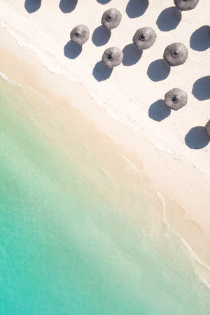 Aerial view of amazing tropical white sandy beach with palm leaves umbrellas and turquoise sea, Mauritius. Stock Photo
