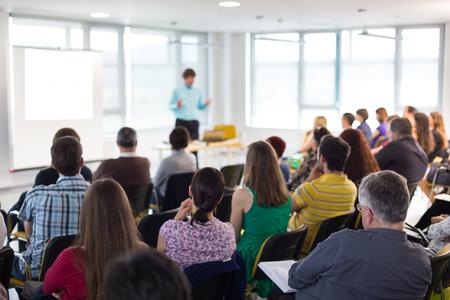 Symposium für Wirtschaft und Unternehmertum. Sprecher, der ein Gespräch beim Geschäftstreffen gibt. Publikum im Konferenzsaal. Rückansicht eines unbekannten Teilnehmers am Publikum. Standard-Bild