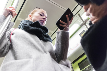 Low angle view of beautiful blonde caucasian woman wearing winter coat and scarf reading on the phone while traveling by metro. Public transport. Imagens