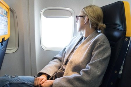 Thoughtful blonde casual caucasian woman wearing glasses, looking through the window while traveling by airplane. Commercial transportation by planes.