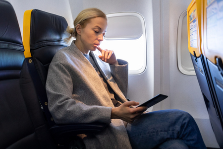 Thoughtful blonde casual caucasian woman reading e-book on digital e-reader while traveling by airplane. Commercial transportation by planes. 写真素材