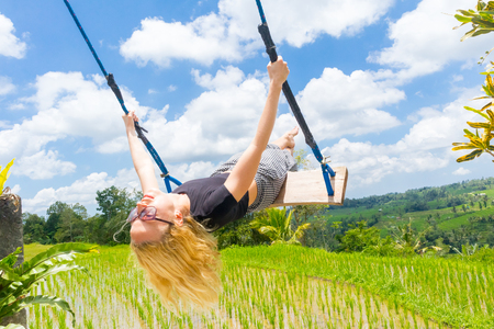 Happy caucasian female traveller swinging on wooden swing, enjoying summer vacation in pristine green nature at Jatiluwih rice terraces on Bali, Indonesia. Freedom and life enjoying concept.