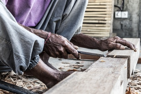 Close up of warn hands of carpenter working with manual tools in traditional carpentry shop in a third world country. Heavy labour intensive manual work.