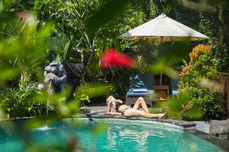 Sensual young woman relaxing in outdoor spa infinity swimming pool surrounded with lush tropical greenery of Ubud, Bali. Wellness, natural beauty and body care concept.