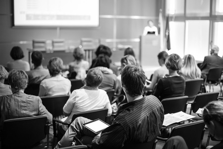 Business and entrepreneurship symposium. Female speaker giving a talk at business meeting. Audience in conference hall. Rear view of unrecognized participant in audience. Black and white image. Фото со стока