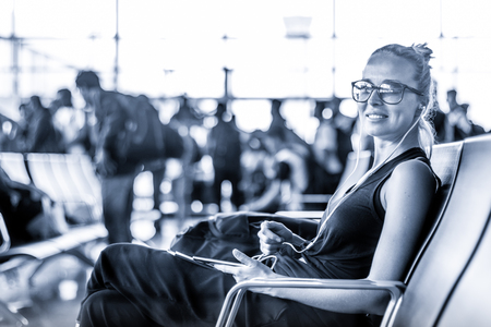 Casual sporty young blond female traveler using her cell phone while waiting to board a plane at the departure gates at the asian airport terminal. Blue toned black and white photo.