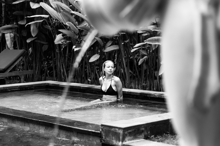 Sensual young woman relaxing in outdoor spa infinity swimming pool surrounded with lush tropical greenery of Ubud, Bali. Wellness, natural beauty and body care concept. Black and white image.