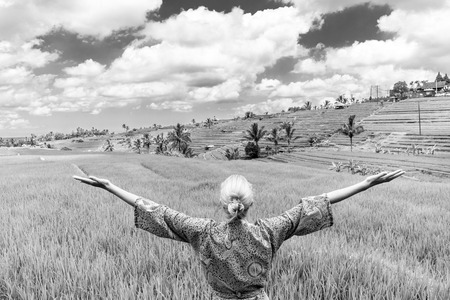 Relaxed fashionable caucasian woman wearing asian style kimono, arms rised to sky, enjoying pure nature at beautiful green rice fields on Bali island. Black and white image.