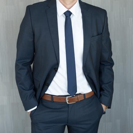 Torso di un impiegato anonimo in piedi con le mani in tasca, che indossa un bellissimo abito blu navy classico alla moda su sfondo grigio. Archivio Fotografico