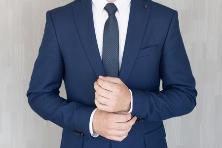 Torso of anonymous businessman wearing beautiful fashionable classic navy blue suit against grey backgound.
