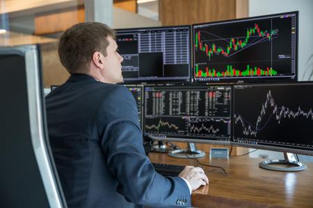 Biznesmen handlu akcjami. Traderzy giełdowi przeglądający wykresy, indeksy, liczby i analizy na wielu ekranach komputerów w nowoczesnym biurze handlowym.