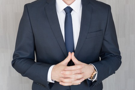Torso of anonymous businessman standing with hands in lowered steeple, wearing beautiful fashionable classic navy blue suit against grey backgound.