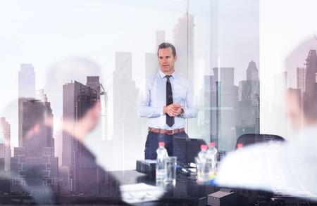 Koncepcja firmy korporacyjnej, rozwoju gospodarczego lub nieruchomości. Przekonany, lider firmy na spotkaniu biznesowym z nowojorskimi budynkami manhattanu i odbiciami okien drapaczy chmur. Zdjęcie Seryjne
