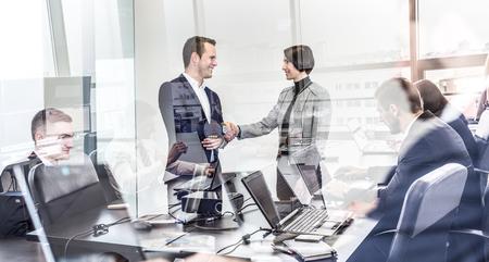 Sigillare un affare. Gli uomini d'affari si stringono la mano, finendo di incontrarsi in ufficio aziendale. Uomini d'affari che lavorano al computer portatile visto nella riflessione di vetro. Concetto di affari e imprenditorialità.