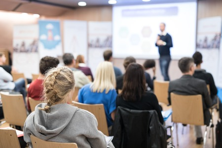 Audience at the conference hall. Speaker giving a talk in conference hall at business event. Business and Entrepreneurship concept. Lens focus on people in audience from rear. Stock Photo