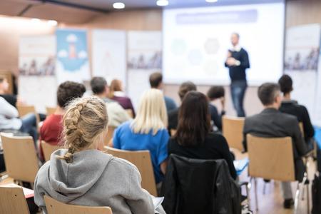 Publiek in de conferentiezaal. Spreker geeft een lezing in de conferentiezaal op een zakelijk evenement. Business en ondernemerschap concept. Lensfocus op mensen in het publiek van achteren. Stockfoto