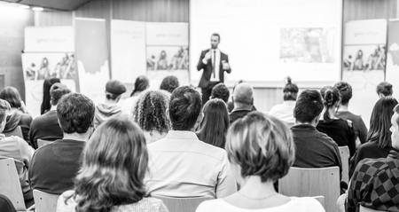 Orador dando charla en evento empresarial. Audiencia en la sala de conferencias. Concepto de negocio y emprendimiento. Concéntrese en personas irreconocibles en la audiencia. En blanco y negro.