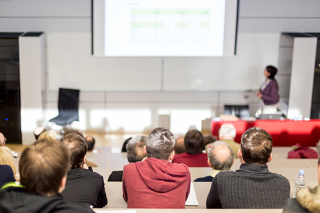 Female speaker giving academic presentation in lecture hall at university workshop. Audience in conference hall. Rear view of unrecognized participant in audience. Scientific conference event. Standard-Bild - 122323029