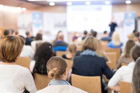 Sprecher hält einen Vortrag im Konferenzsaal bei einer Geschäftsveranstaltung. Publikum im Konferenzsaal. Business- und Entrepreneurship-Konzept. Konzentrieren Sie sich auf nicht erkennbare Personen im Publikum. Standard-Bild