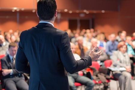 Spreker houdt een toespraak op zakelijke bijeenkomst. Onherkenbare mensen in het publiek in de conferentiezaal. Bedrijfs- en ondernemerschapsevenement. Stockfoto