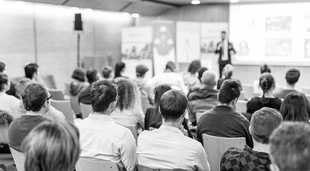 Speaker giving talk at business event. Audience at the conference hall. Business and Entrepreneurship concept. Focus on unrecognizable people in audience. Black and white. 写真素材