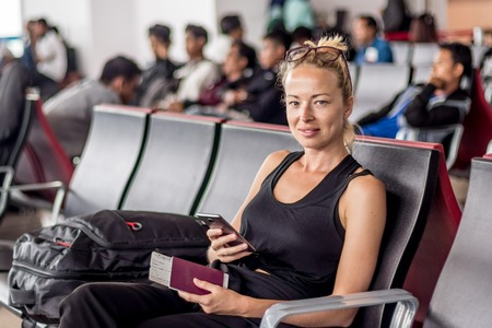 Casual tanned blond female traveler holding cell phone, passport and boarding pass while waiting to board a plane at the departure gates at the asian airport terminal.