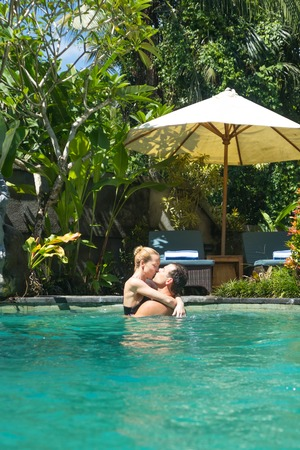 Happy couple kissing while relaxing in outdoor spa infinity swimming pool surrounded with lush tropical greenery of Ubud, Bali. Luxury spa and wellness vacation retreat concept.
